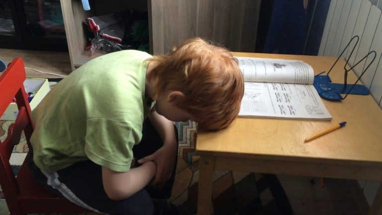 Втомлений хлопчик робить домашнє завдання