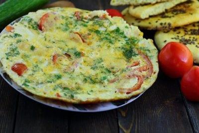 Омлет з помідорами, ковбасою і сиром на сковороді